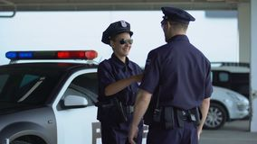 Male and female police officers giving high five communicating on parking lot. Stock footage stock video