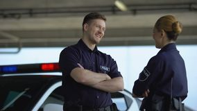 Male and female police officers giving high five, satisfied with good job, duty. Stock footage stock video