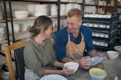 Male and female potter interacting while decorating earthenware Royalty Free Stock Photo