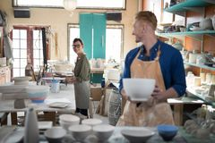 Male and female potter interacting while working. In pottery shop Royalty Free Stock Photo