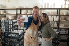 Male and female potter taking selfie with mobile phone. In pottery workshop Stock Photography