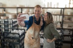 Male and female potter taking selfie with mobile phone. In pottery workshop Royalty Free Stock Photo