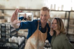 Male and female potter taking selfie with mobile phone. In pottery workshop Royalty Free Stock Images