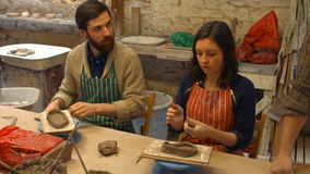 Male and female potters molding a clay stock footage