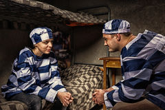 Male and female prisoners wearing prison uniform sitting and loo. Male and female prisoners wearing prison uniform sitting near bedside table and looking at each Royalty Free Stock Photo