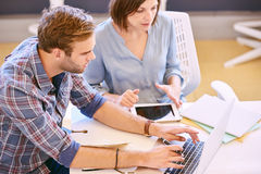 Male and female professional working together to achieve more. Male business person types on the keyboard of his laptop computer as his female business associate Stock Image