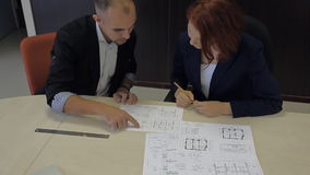 Male and female professionals working together on. Confident businesswoman and her partner are working together on a project that blueprint on the table with the stock video