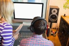 Male and female radio hosts in studio Stock Image