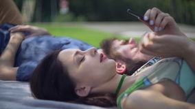 Male and female relax outdoors with modern device. stock video footage