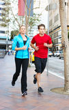 Male And Female Runners On Urban Street Stock Photo