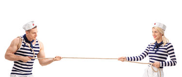 Male and a female sailor playing tug-of-war Royalty Free Stock Image