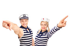 Male and female sailor pointing up with their fingers. And looking at the camera isolated on white background Royalty Free Stock Photos