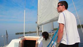 Male and female sailors navigate sailing yacht. Making a turn. Stock footage stock video