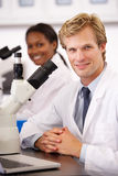 Male And Female Scientists Using Microscopes In Laboratory. Smiling Stock Photos