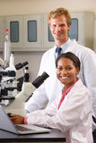 Male And Female Scientists Using Microscopes In Laboratory. Smiling At Camera Stock Photos