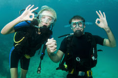 Male and female scuba dive together. Man and wife scuba dive together in the ocean stock photography