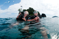 Male and female scuba dive together. Man and wife scuba dive together in the ocean on the surface royalty free stock photo