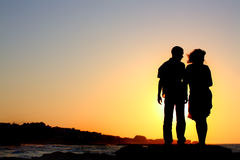 Male and female by the sea silhouette. Silhouette of a male and female standing by the sea Royalty Free Stock Photos