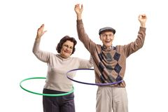 Male and female seniors with hula-hoops dancing. Isolated on white background stock photos