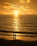 Couple meets on the beach at sunset. Male and female silhouettes meet at romantic sunset beach stock photography