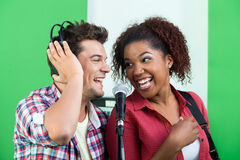 Male And Female Singers Performing While Looking At Each Other. Excited male and female singers performing while looking at each other in recording studio Stock Image
