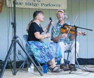 Male and Female Singing. Roanoke, VA – September 24th: Male and Female member of the Indian Run String Band singing at the Roanoke Mountain Campground located Royalty Free Stock Images