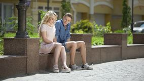Male and female sitting on bench next to each other, feeling awkward, first date. Stock footage stock video
