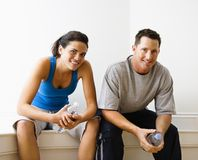 Male and female sitting smiling. Royalty Free Stock Photography
