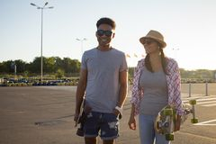 Male and female skateboarders having fun in morning mall parking. Happy young couple with skateboard, concept of happiness, love and youth Stock Images