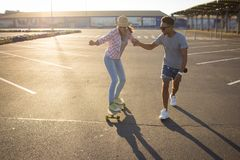 Male and female skateboarders having fun in morning mall parking. Happy young couple with skateboard, concept of happiness, love and youth Stock Photo