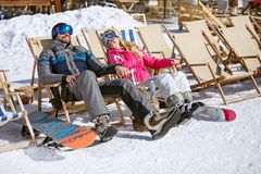 Male and female skiers enjoy in sun loungers. On ski terrain stock image