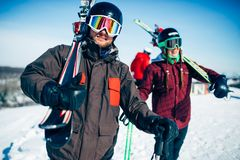 Male and female skiers poses with skis and poles. In hands, blue sky and snowy mountains on background. Winter active sport, extreme lifestyle. Downhill skiing Stock Photo