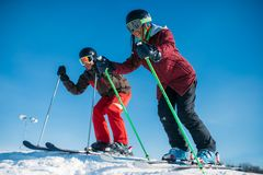 Male and female skiers racing from the mountain. Side view. Winter active sport, extreme lifestyle. Downhill skiing Royalty Free Stock Image