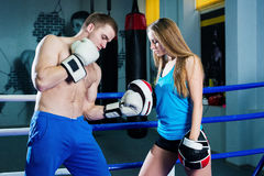 Male and female sporty couple practicing boxing at the gym at boxing ring. Royalty Free Stock Photography