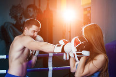 Male and female sporty couple practicing boxing at the gym at boxing ring. Royalty Free Stock Images