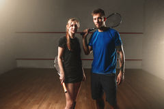 Male and female squash game players with rackets. Young couple in sportswear with racquets, indoor sport club Stock Image