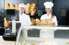 Male and female staff offering fresh baguettes. Happy male and young female staff offering fresh baguettes and buns in bakery Royalty Free Stock Photo