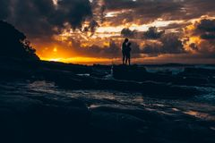 Male and female standing on stone at night coast stock photos