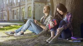 Male and female strangers sitting under tree, first meeting, indecisiveness. Stock footage Royalty Free Stock Photo