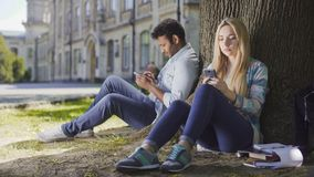 Male, female strangers sitting under tree, using smartphone, girl looking upset. Stock footage Royalty Free Stock Photos