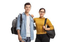 Male and a female student with backpacks smiling at the camera royalty free stock image