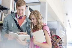 Male and female students discussing over books by shelf at university library stock photography