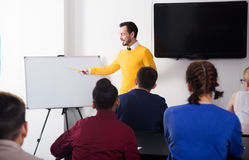 Male and female students following explanations of teacher. In class Stock Photography