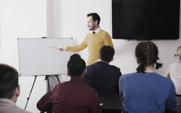 Male and female students following explanations of teacher. In class Stock Image