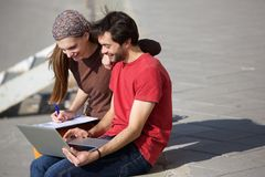 Male and female students sitting outdoors looking at laptop. Portrait of a young male and female students sitting outdoors looking at laptop Royalty Free Stock Image