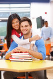 Male And Female Students Studying In Classroom With Books. Hugging Each Over Royalty Free Stock Images