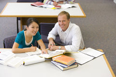 Male and female students studying at table, smiling, portrait, elevated view royalty free stock photo