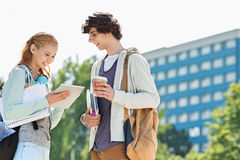 Male and female students using digital tablet at college campus Stock Photo