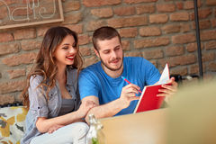Male and female students write and learn in cafe Royalty Free Stock Photo