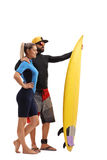 Male and female surfer posing with a surfboard. Full length profile shot of a male and female surfer posing with a surfboard isolated on white background Royalty Free Stock Photos